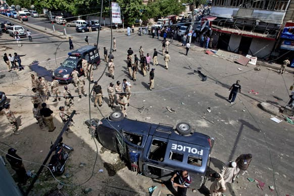 Pakistani security men gather at the site of a bomb blast in Karachi. A bomb targeting a senior judge in the southern Pakistani city of Karachi wounded him and killed several security personnel.