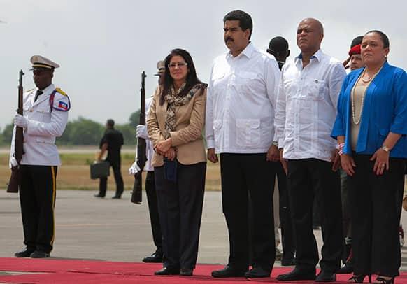 Venezuela`s First Lady Cilia Flores, left, Venezuela`s President Nicolas Maduro, second from left, Haiti`s President Michel Martelly, second from right, and Haiti`s First Lady Sophia Martelly listen to Haiti`s national anthem at Toussaint Louverture airport in Port-au-Prince, Haiti.