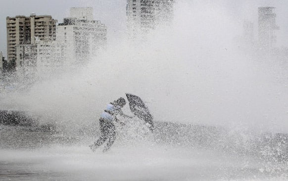 A man struggles with his umbrella as waves lash the shore during high tide in Mumbai.