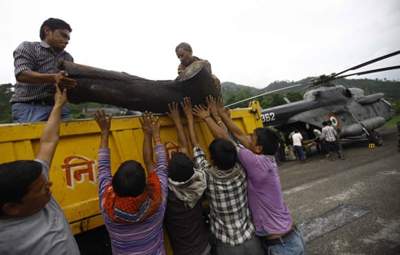 Locals unload a large piece of wood from a truck to be placed on to an Indian Air force helicopter as cremation efforts for those killed in landslides and monsoon floods are underway, in Gauchar, in Uttarakhand.
