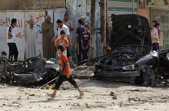 Iraqis inspect the aftermath of a car bomb attack at Baghdad`s mostly Shiite neighborhood of Husseiniyah, Iraq.