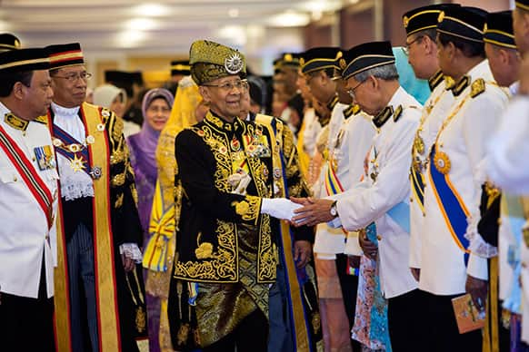 Malaysian King Sultan Abdul Halim Mu`adzam Shah, center, shakes hands with members of Parliament during the opening of the 13th parliament session at the Parliament house in Kuala Lumpur, Malaysia.