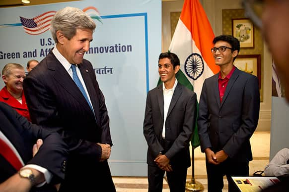 John Kerry jokes with Nahush Katti and Vikram Arun, of DoctorOn LLC, who both recently graduated high school and will attend universities in the US, after listening to presentations from Indian inventors during a tour of exhibits in the