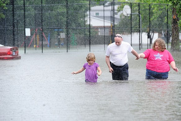 James Gregory and his daughters Autumn and Rayanna wade through water on Coventry Court in their east side apartment complex, Ashley Pointe, in Evansville, Ind. after they try to get back home because the roads were impassable.
