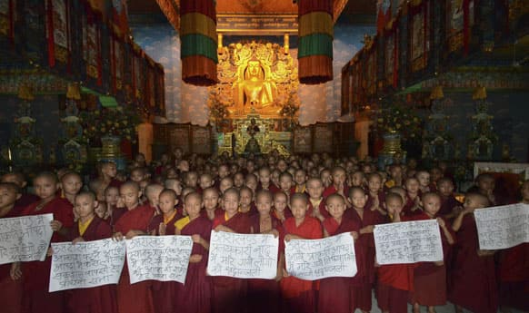 Young Buddhist monks gather at Tergar Monastery to pray for the flood victims of northern Indian state of Uttarakhand, in Bodhgaya.
