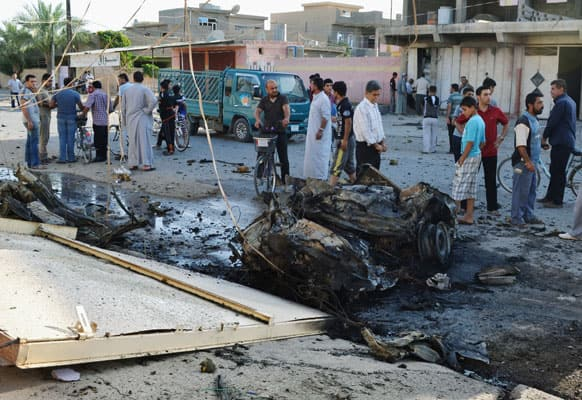 Civilians inspect the scene of two parked car bombs in the early morning at a residential area in Tuz Khormato, 130 miles (210 kilometers) north of Baghdad, Iraq.