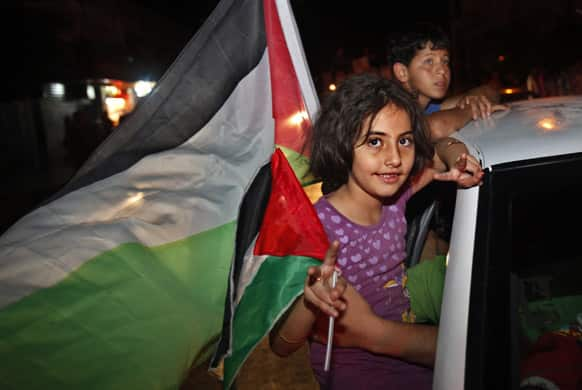 A Palestinian girl waves a national flag while celebrating after Palestinian singer Mohammed Assaf won a regional TV singing contest, along the streets of Gaza City.