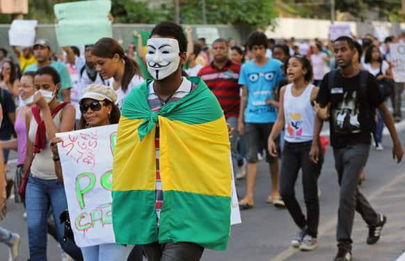 A masked demonstrator carries a Brazilian flag on his back near the Arena Fonte Nova stadium in Salvador, Brazil.