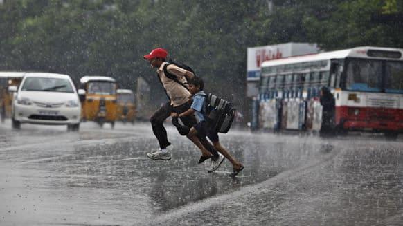 School children run to cross a street during rains in Hyderabad.