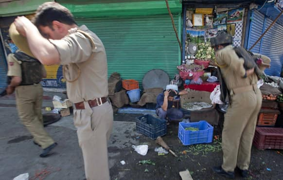 A Kashmiri shopkeeper reacts in fear as policemen arrive near the site of a shootout in Srinagar. A top police official said suspected militants have shot and killed two police officers in Kashmir.