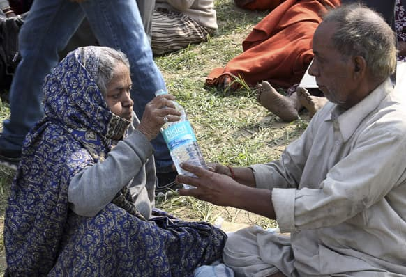 An elderly couple help each other to drink water before being evacuated from the upper reaches of mountains, in Gaurikund, Uttrakhand.