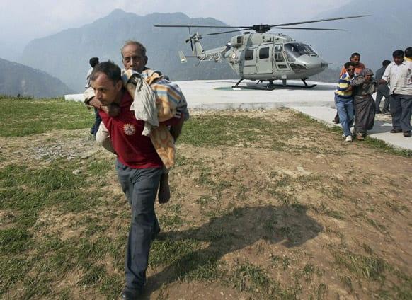 Rescued flood affected pilgrims alight from a chopper in Guptkashi, Uttarakhand.