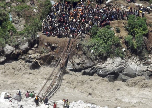 Indo-Tibetan Border Police (ITBP) personnel help stranded pilgrims on a makeshift bridge cross a stream of gushing floodwater at Govind Ghati, in Chamoli district, in Uttarakhand.