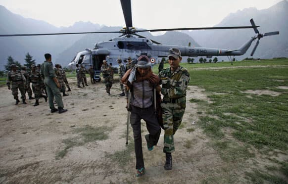 An Indian army soldier helps a flood affected man after being evacuated by a helicopter from the upper reaches of mountains in Joshimath.