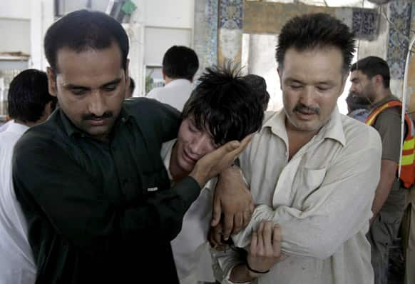 People comfort a boy who lost his family member in a suicide bombing at a Shiite mosque in Peshawar.