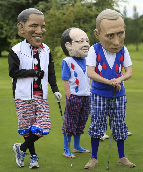 Members of the NGO group Oxfam, dressed in golf clothes and wearing paper mache masks, imitate G-8 leaders during a demonstration at the Enniskillen Golf course near the venue of the G-8 summit in Enniskillen, Northern Ireland.