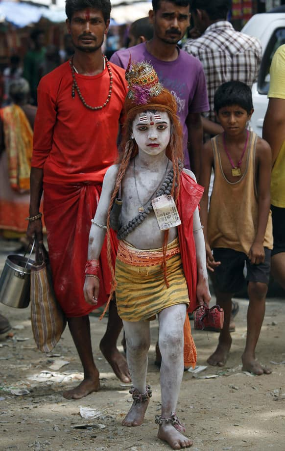 A young Indian child, dressed like Lord Shiva, stands among devotees at the Kamakhya temple in Guwahati.