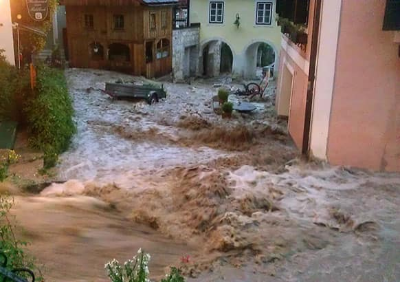 In this picture provided by Hallstatt.net flood rushes down a street in the village of Hallstatt, Austria.