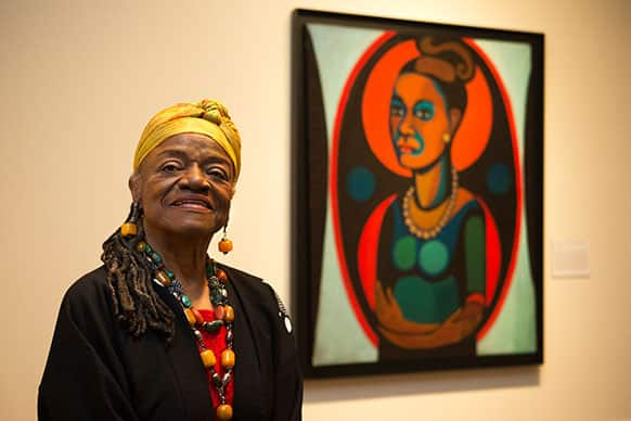 Artist Faith Ringgold poses for a portrait in front of a painted self-portrait during a press preview of her exhibition,