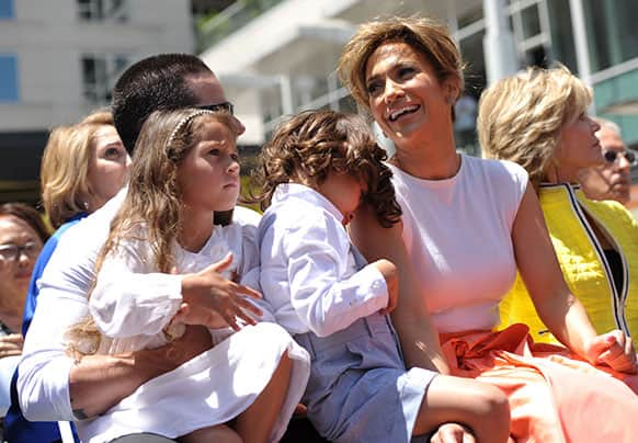 Actress and singer Jennifer Lopez,  appears with her twins Emme Marbiel Muniz, and Maximilian David Muniz, on the lap of Casper Smart at a ceremony honoring her on the Hollywood Walk of Fame in Los Angeles.