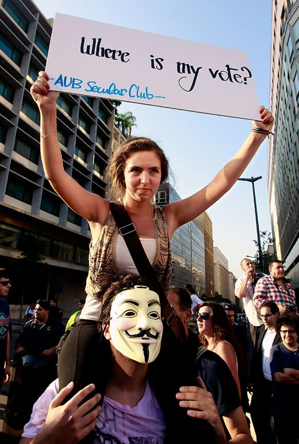 A protester holds a placard during a demonstration protesting the extension of the parliament's mandate, in Beirut, Lebanon.