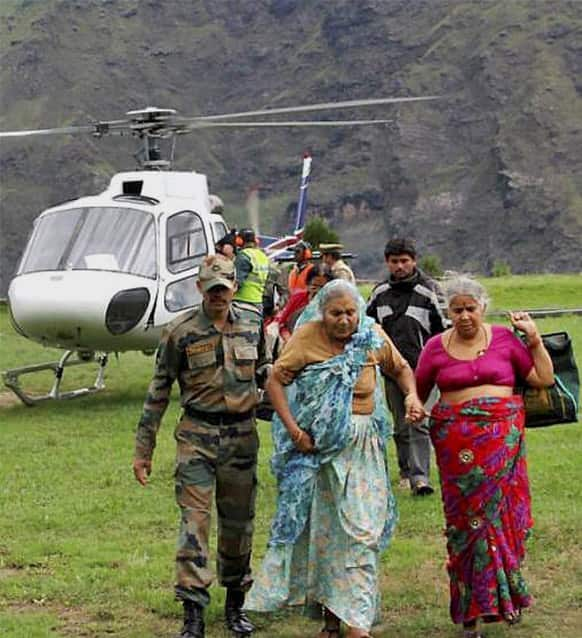 Army soldier helps flood affected elderly pilgrims after being evacuated from upper reaches of mountains, in Chamoli, in Indian northern state of Uttrakhand.