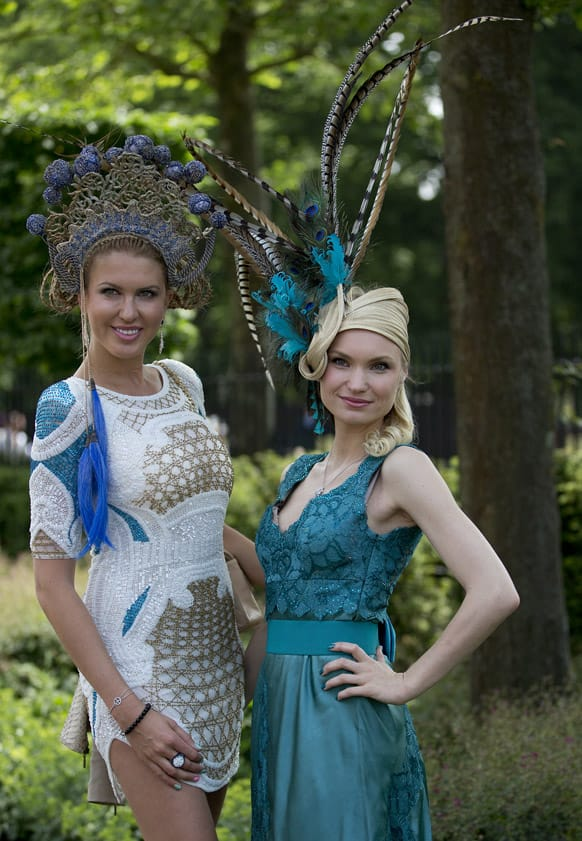 Marinilia Smirnova, right, and Natalia Kapchuck pose for the media wearing ornate hats on the second day of the Royal Ascot horse race meeting in Ascot, England.