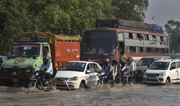 Commuters travel on a flooded road after a rise in the water levels of the Yamuna River in New Delhi. The latest rains have affected several states and the capital, New Delhi, where nearly 2,000 people were evacuated to government-run camps on higher ground.