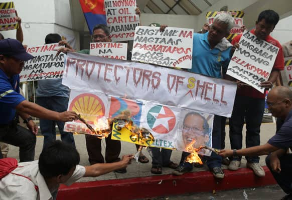 Filipino members of a drivers and operators group light a slogan bearing logos of oil companies and a picture of Philippine President Benigno Aquino III as they hold a rally outside the office of Shell at the financial district of Makati, south of Manila.