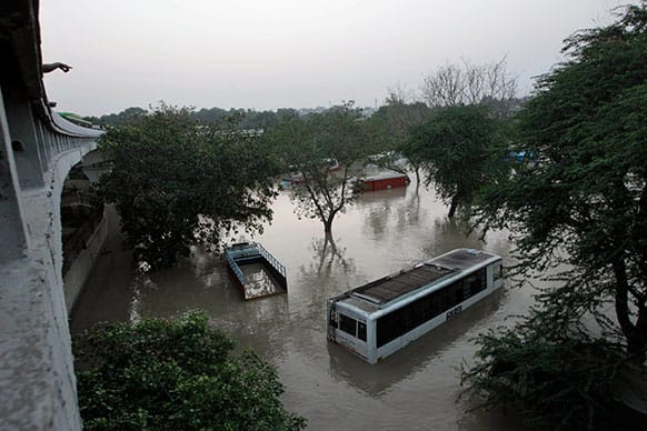 Buses and trucks are submerged in the rising waters of the Yamuna River in New Delhi.