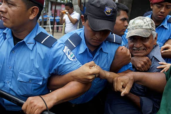 A members of the National Elderly Unit, right, clashs with police during a protest in front of the Social Security building to demand their pensions in Managua, Nicaragua.