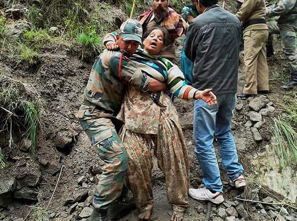 An Indian army personnel carries a stranded woman pilgrim to a safer area in Chamoli district, in the northern Indian state of Uttarakhand.