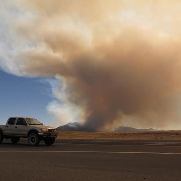 A truck moves past the so-called Doce fire near Prescott, Ariz.