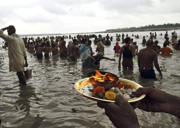 A Hindu devotee offers morning prayers on the banks of the River Ganges in Allahabad. Hindus across the country are celebrating Ganga Dussehra, devoted to the worship of the River Ganges.