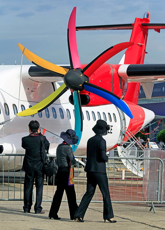 Visitors watch the multicolor propeller of an ATR 72-600 jet of Colombian company Avianca, at the 50th Paris Air Show at Le Bourget airport, north of Paris.