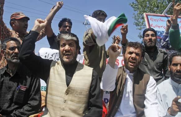 Chairman of Democratic Freedom Party and senior separatist leader Shabir Ahmad Shah, with Javid Mir, shout slogans during a protest in Srinagar.