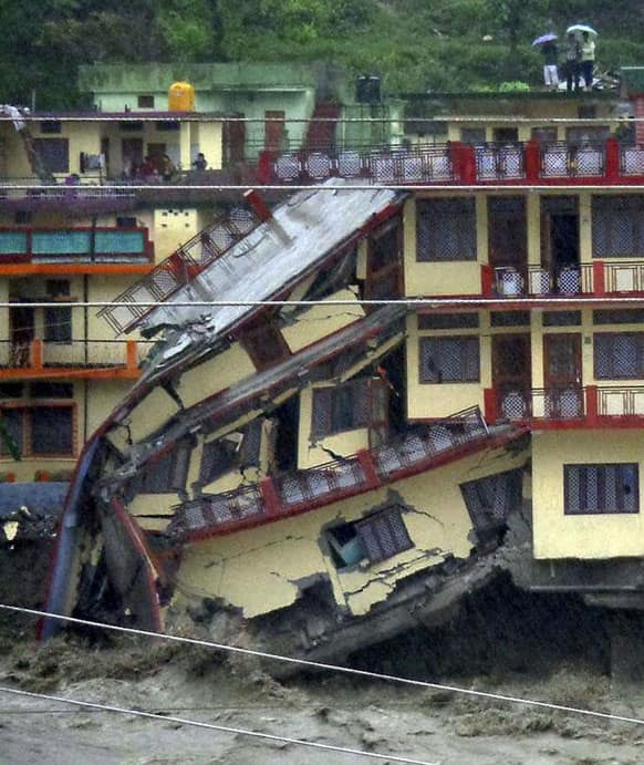 A three-story building is destroyed by floodwaters, in Uttarkashi, in northern Indian state of Uttarakhand.