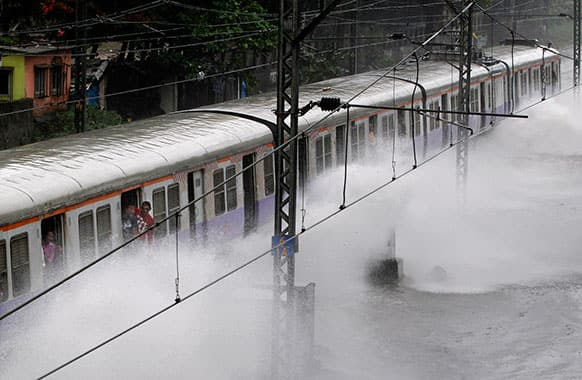 A local train moves through a flooded railway track after heavy rains in Mumbai.