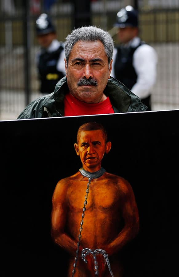 Political painter Kaya Mar, 56, poses with his latest painting depicting US President Barack Obama as a slave, during a protest against western intervention in Syria, outside the US embassy in central London.