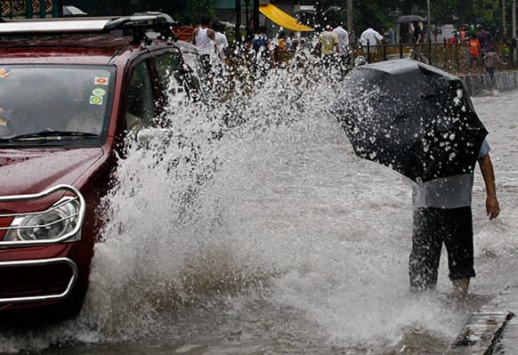 A car makes its way through a flooded road during heavy rains as a man walks in Mumbai.