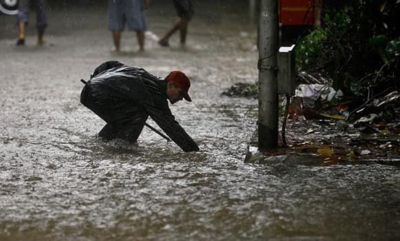 A local municipal worker cleans a manhole on a waterlogged street in the rain in Mumbai.