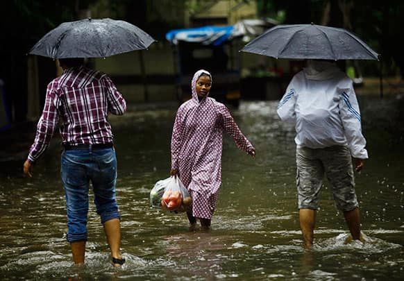 People walk through a flooded street during monsoon rains in Mumbai.