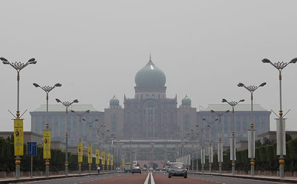 Motorists drive vehicles near the prime minister`s office on a hazy day in Putrajaya, Malaysia.
