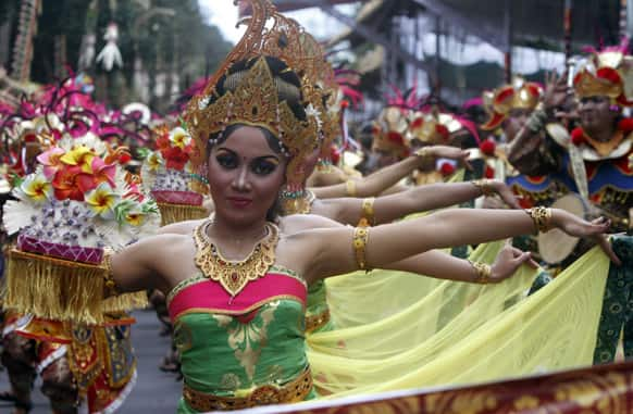 Indonesian dancers in traditional outfit perform during a parade to mark the 35th Bali Arts Festival in Denpasar, Bali, Indonesia.
