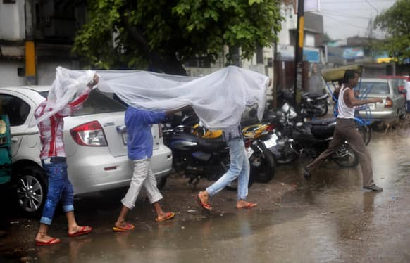Men cover themselves with a plastic sheet as it rains in New Delhi.