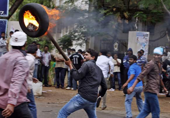 """A student holds a burning tire with a rod during a protest demanding creation of a new state named """"Telangana"""" in Hyderabad."""