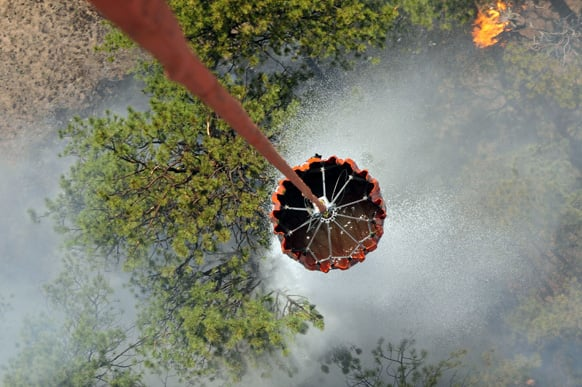 Water is released from a helicopter bucket over fires in the Black Forest area northeast of Colorado Springs, Colo. More than 350 homes have been lost in what is now the most destructive wildfire in Colorado history.