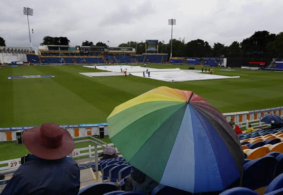 Spectators shelter from the weather as rain delayed the start of the ICC Champions Trophy cricket match between West Indies and South Africa at the Cardiff Wales Stadium in Cardiff.