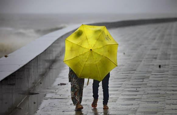 Two girls hold an umbrella while visiting the Arabian Sea coast as it rains in Mumbai.