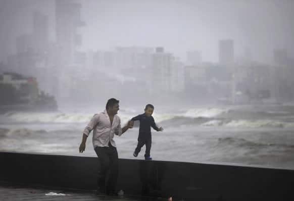 A father and son enjoy high tidal waves during monsoon rains on the Arabian Sea coast in Mumbai.